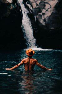 Man in hat in a waterfall